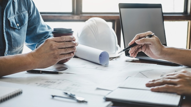 Conceito de construção e estrutura de reunião de engenheiro ou arquiteto para projeto trabalhando com parceiro e ferramentas de engenharia na construção da maquete e planta no canteiro de obras, contrato para ambas as empresas. Foto Premium