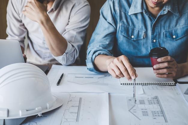 Conceito de construção e estrutura de reunião de engenheiro ou arquiteto para projeto trabalhando com parceiro e ferramentas de engenharia na construção de modelo e blueprint no local de trabalho, contrato para ambas as empresas
