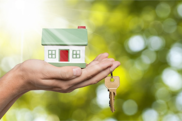 Conceito de construção, hipoteca, imobiliário e propriedade - feche a mão segurando o modelo e as chaves da casa