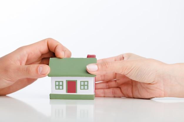 Conceito de construção, hipoteca, imóveis e propriedade - fechar as mãos com o modelo da casa