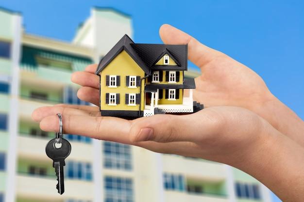 Conceito de construção, hipoteca, imóveis e propriedade - feche a mão segurando o modelo da casa