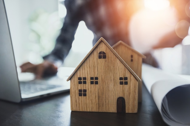 Conceito de construção imobiliária, modelo de madeira com engenheiro ou arquiteto planejando e trabalhando no fundo do laptop