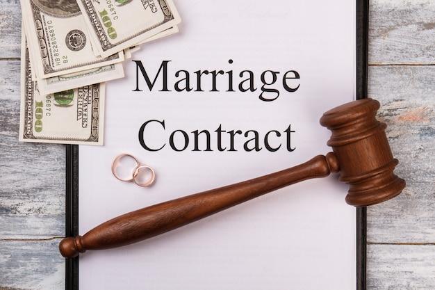 Conceito de contrato de casamento. alianças de madeira do martelo e vista superior do dinheiro.