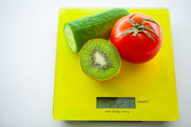 Conceito de controle de dieta ou peso. frutas e legumes com fita métrica na escala de peso. fitness e conceito de dieta alimentar saudável.
