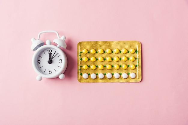 Conceito de controle de natalidade de remédio, despertador e pílulas anticoncepcionais