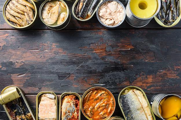Conceito de copyspace para texto entre duas linhas de vários legumes enlatados preparados, carne, peixe e frutas em latas. em uma vista superior do plano de fundo de madeira