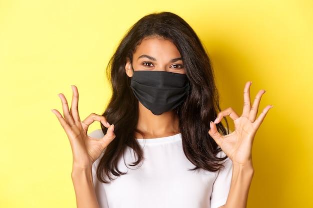 Conceito de coronavírus, pandemia e estilo de vida. close-up de uma mulher afro-americana confiante e sorridente na máscara facial preta, mostrando sinais de aprovação, como algo bom, fundo amarelo.
