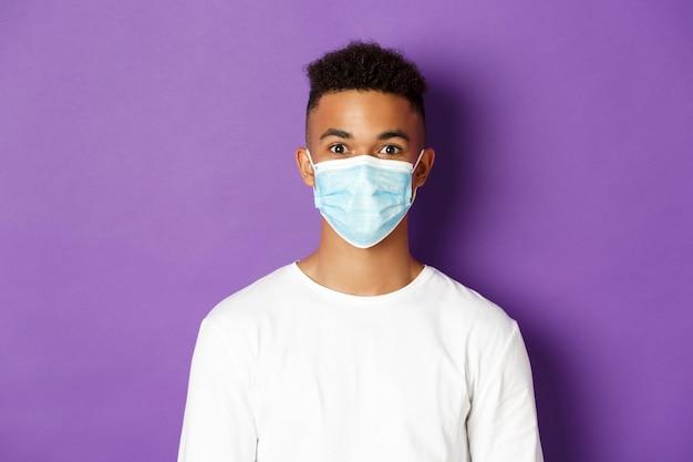 Conceito de coronavírus, quarentena e distanciamento social. close-up de um jovem afro-americano de moletom branco e máscara médica, olhando para a câmera, em pé sobre um fundo roxo.