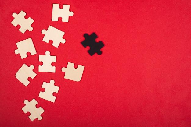 Conceito de corvo branco, pária, quebra-cabeças, conceito de negócios sobre fundo vermelho.