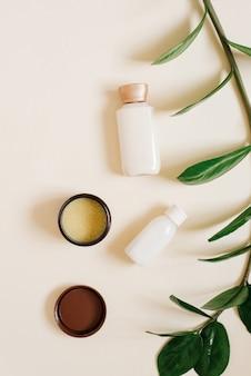 Conceito de cosméticos orgânicos à base de plantas. garrafas com creme para o corpo ou rosto, manteiga de cacau sólida em frasco aberto e um galho de planta tropical sobre fundo bege.