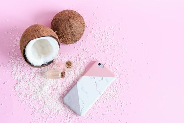 Conceito de cosméticos orgânicos com coco em fundo rosa. coco fresco, óleo de coco e smartfon moderno em estojo elegante, vista superior.