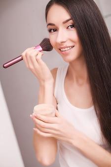 Conceito de cosméticos, saúde e beleza - mulher bonita com os olhos fechados e pincel de maquiagem