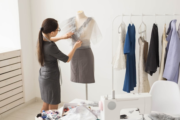 Conceito de costureira, alfaiate, moda e showroom - retrato de talentosa costureira que trabalha com têxteis para costurar roupas.