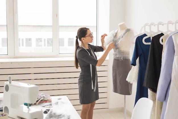 Conceito de costureira, alfaiate, moda e showroom - visão lateral de estilista de moda feminina medindo