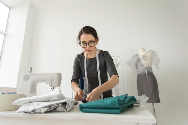 Conceito de costureira, estilista, alfaiate e pessoas - retrato de uma costureira no trabalho.