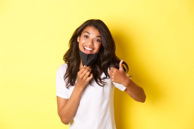 Conceito de covid-19, distanciamento social e estilo de vida. retrato de uma mulher atraente afro-americana, sorrindo, decolando a máscara facial e mostrando o polegar para cima, recomendo algo.
