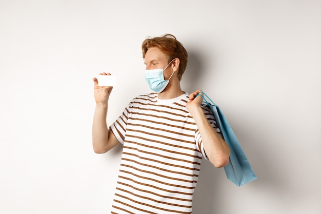 Conceito de covid-19 e compras. feliz jovem comprador com máscara facial segurando um saco de papel e mostrando um cartão de crédito de plástico, comprando com descontos, fundo branco