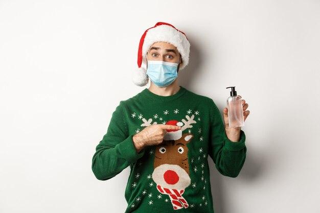 Conceito de covid-19 e férias de natal com jovem bonito usando uma máscara. jovem com máscara médica oferece um anti-séptico, apontando para a mão desinfetante, usando chapéu de papai noel, fundo branco.