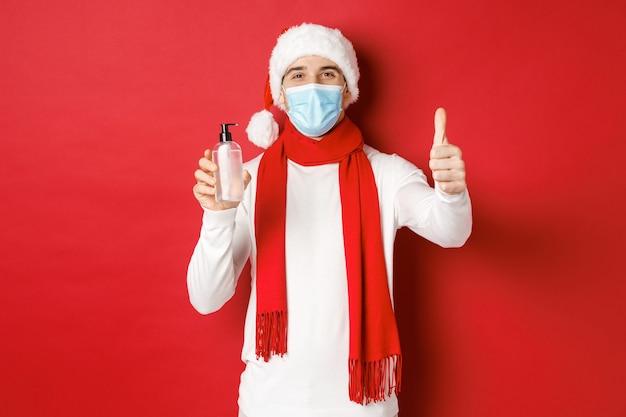 Conceito de covid natal e feriados durante a pandemia de homem feliz e satisfeito no chapéu de papai noel e med ...