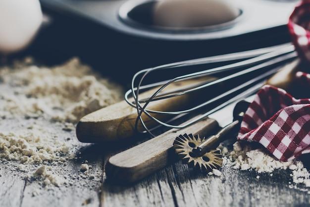 Conceito de cozimento cozinha utensílios de cozinha acessórios para assar no fundo de madeira com farinha. fechar-se. processo de cozimento.