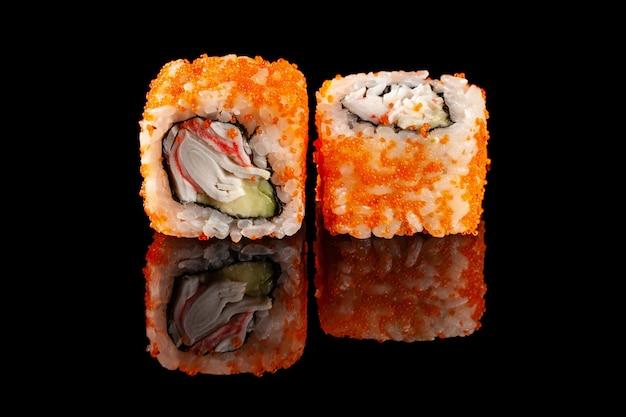 Conceito de cozinha asiática. dois rolos do sushi com enchimentos diferentes em um fundo preto com a idade para um menu japonês para um café, restaurante, barra de sushi.