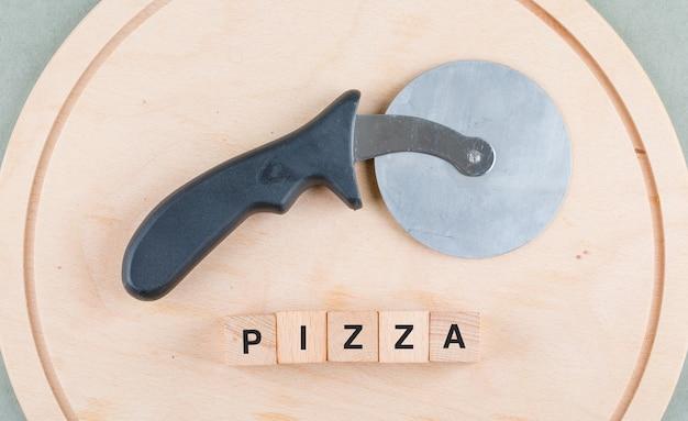 Conceito de cozinha com blocos de madeira com palavras, vista superior do cortador de pizza.