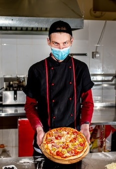 Conceito de cozinha de pizza, chef com máscara médica coloca ingredientes na pizza