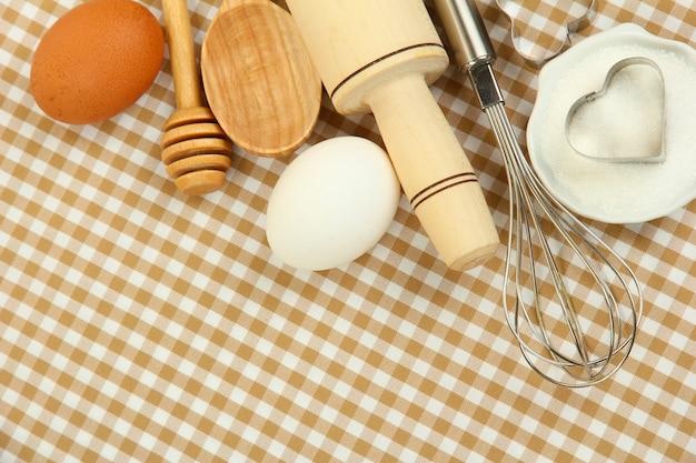 Conceito de cozinha. ingredientes básicos de panificação e utensílios de cozinha na superfície da toalha de mesa