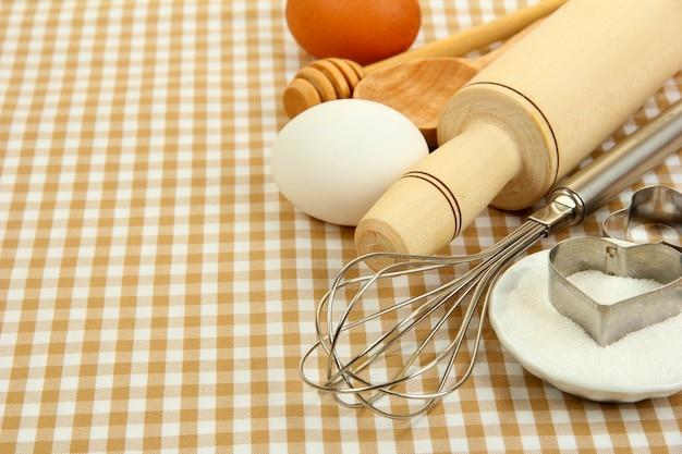 Conceito de cozinha. ingredientes básicos de panificação e utensílios de cozinha na toalha de mesa