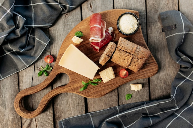 Conceito de cozinha italiana plana leigos. tábua de cortar, pedaços de queijo parmesão, queijo ralado em uma tigela preta