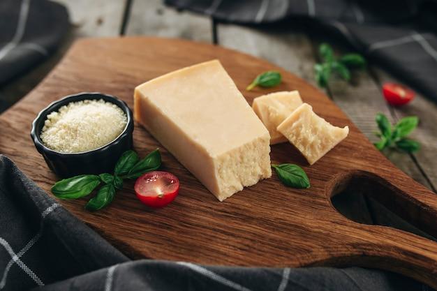 Conceito de cozinha italiana. tábua de corte, pedaços de queijo parmesão, queijo ralado em uma tigela preta pequena, tomates cereja, ramos de folhas de manjericão, toalha de cozinha na mesa de madeira. alimentação saudável