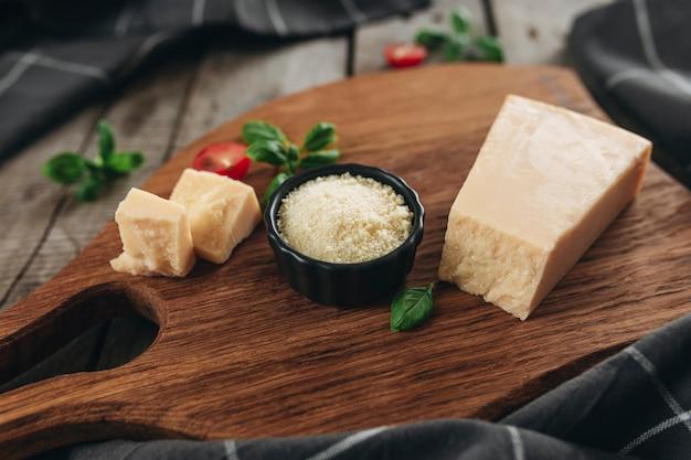 Conceito de cozinha italiana. tábua de corte, pedaços de queijo parmesão, queijo ralado em uma tigela preta pequena, tomates cereja, ramos de folhas de manjericão, toalha de cozinha na mesa de madeira. conceito de alimentação saudável