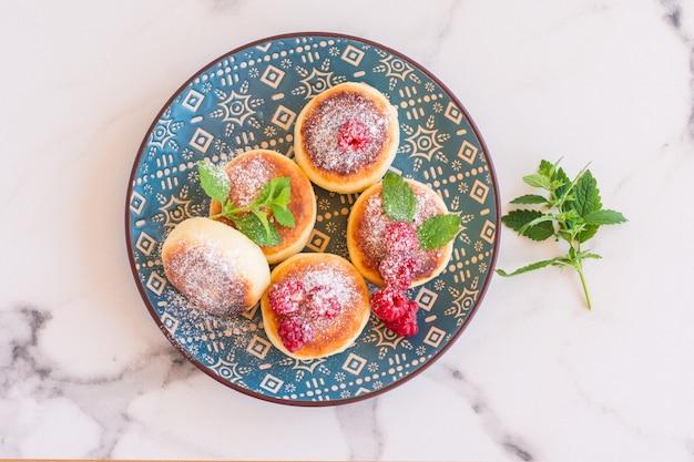 Conceito de cozinha russa e ucraniana. panquecas de queijo cottage. cheesecakes com framboesa e hortelã no prato