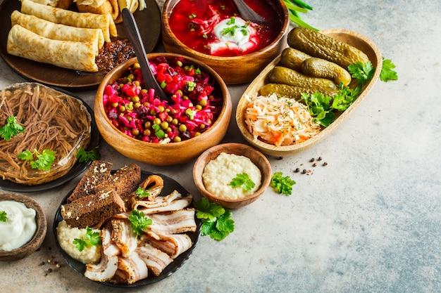 Conceito de cozinha tradicional russa. borsch, gelatina, carne, banha, crepes, vinagrete de salada e chucrute, fundo cinza.