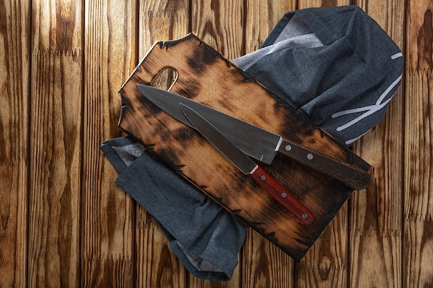 Conceito de cozinhar, cozinhar. duas facas de cozinha em uma placa de corte e um guardanapo em uma mesa de madeira, vista aérea.