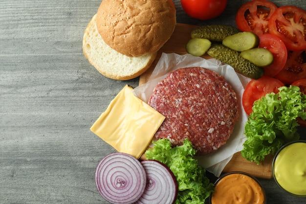 Conceito de cozinhar hambúrguer em mesa texturizada cinza