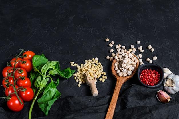 Conceito de cozinhar húmus. ingredientes: alho, grão de bico, pinhões, manjericão, pimenta. fundo preto. vista do topo.