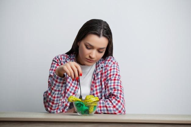 Conceito de crescente mulher magra com o prato cheio de fita métrica