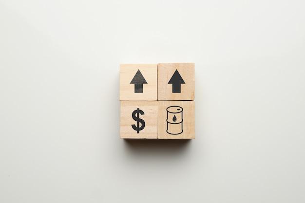Conceito de crescimento de petróleo e dólares com ícones em blocos de madeira.