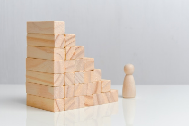Conceito de crescimento de requisitos para um funcionário. blocos de madeira em um espaço em branco.