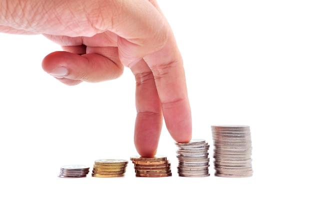 Conceito de crescimento. dedos subindo em pilhas de moedas sobre fundo branco