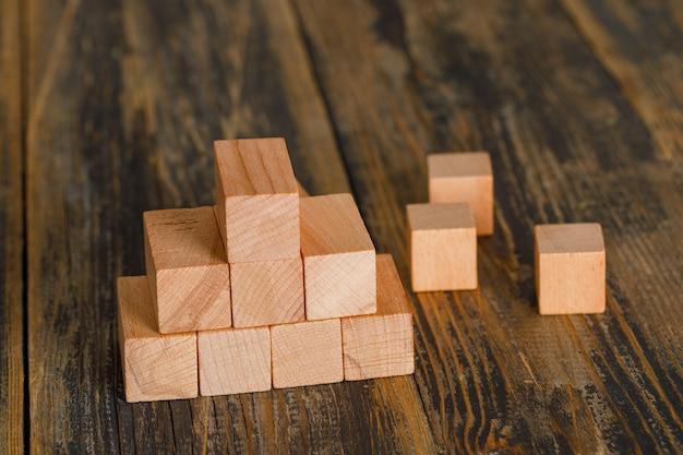 Conceito de crescimento do negócio com a pirâmide de cubos de madeira na opinião de ângulo alto da mesa de madeira.
