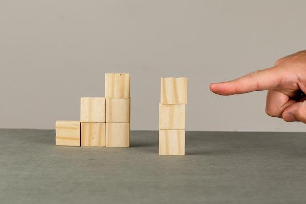 Conceito de crescimento do negócio na opinião lateral da parede cinza e branca. homem mostrando a torre de blocos de madeira.