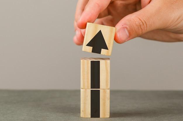 Conceito de crescimento do negócio na opinião lateral da parede cinza e branca. mão colocando o bloco de madeira na torre.