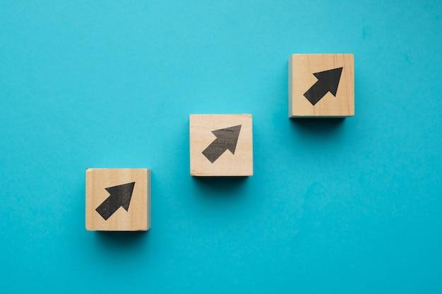 Conceito de crescimento financeiro com ícones em blocos de madeira.