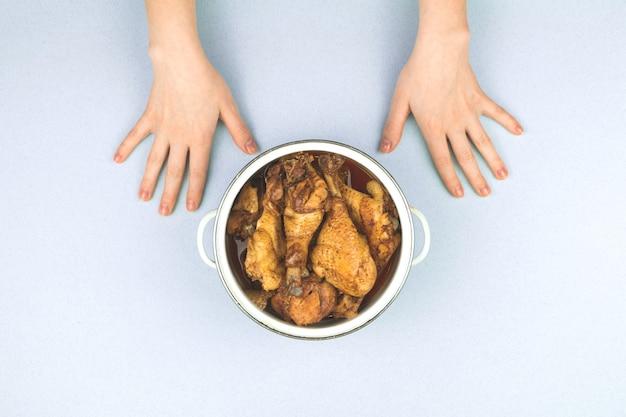 Conceito de criança feliz esperando para começar o jantar, frango assado em uma panela, criança com fome, foto vista de cima