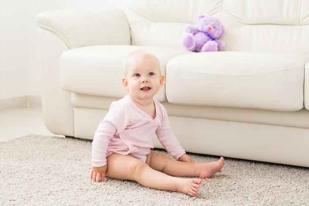 Conceito de crianças, bebês e infância - lindo e sorridente bebê sentado