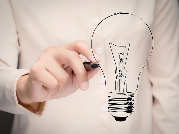 Conceito de criatividade com a mão de uma mulher desenhando uma lâmpada.