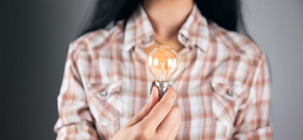 Conceito de criatividade de ideias, mulher segurando uma lâmpada