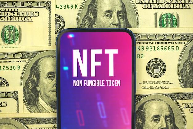 Conceito de criptoarte e tecnologia, logotipo do token nft no celular, nova criptomoeda virtual, banco e blockchain, dólares no fundo, foto da vista superior